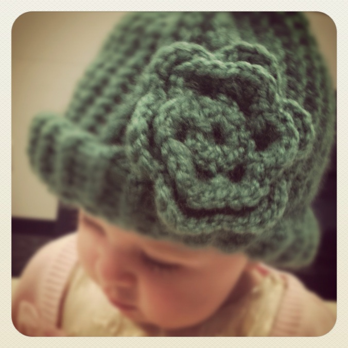 baby wearing a knotted cap with crocheted flower
